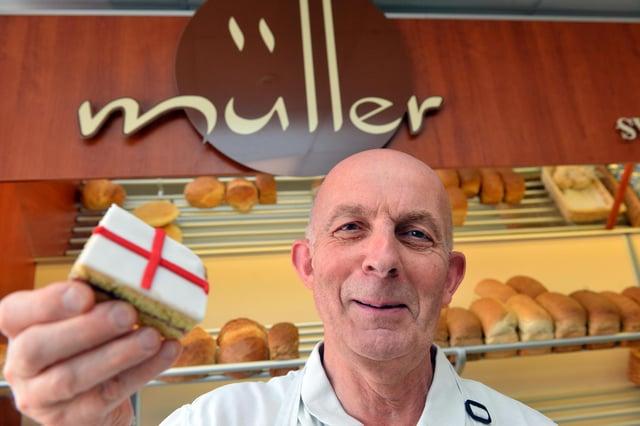 Bruno Muller, proprietario di Muller Baker, tiene in mano una fetta rosa di St George's Cross prima della finale di EURO Inghilterra V Italia.