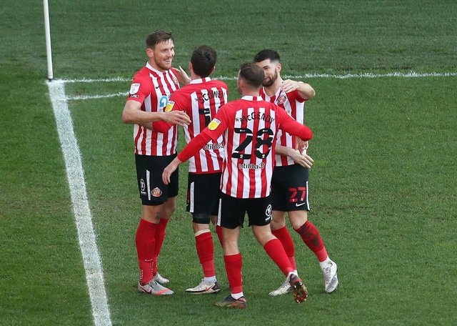 Charlie Wyke of Sunderland celebrates with Josh Scowen, Aiden McGeady and Jordan Jones after scoring their side's first goal during the Sky Bet League One match between Wigan Athletic and Sunderland at DW Stadium