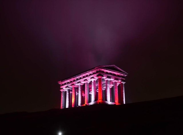 Penshaw Monument lit up in red and white