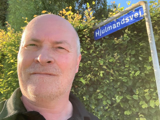 Søren Plovgaard next to an Assens street sign which has the name of the Denmark coach.