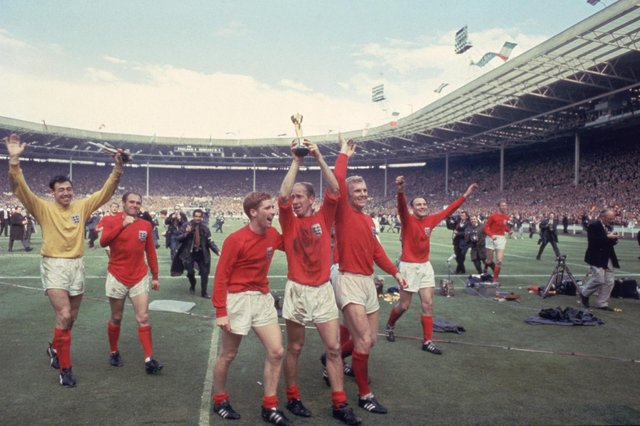 Bobby Charlton raises the Jules Rimet trophy in the air  following England's 4-2 victory after extra time over West Germany in the World Cup Final at Wembley Stadium, 30th July 1966. Amongst his team mates celebrating with him are goalkeeper Gordon Banks, Alan Ball on his right and team captain Bobby Moore (1941 - 1993) at his left. (Photo by Hulton Archive/Getty Images)