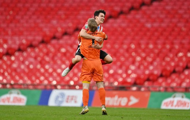 Lee Burge of Sunderland celebrates victory with team mate Luke O'Nien following the Papa John's Trophy Final match between Sunderland and Tranmere Rovers.