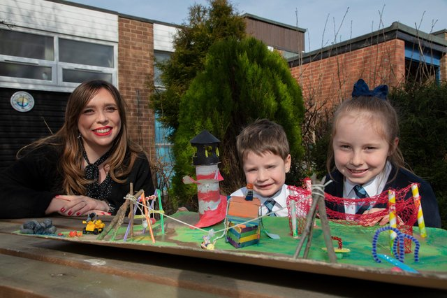 Councillor Rebecca Atkinson with competition winners Sophia and Henry Nixon and their 3D design of the new play park.