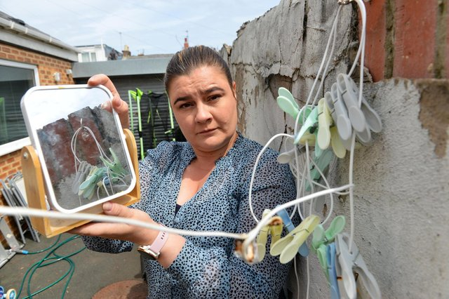 Emma Krieger with the mirror that caused a fire to her washing line by the reflection off the sun.