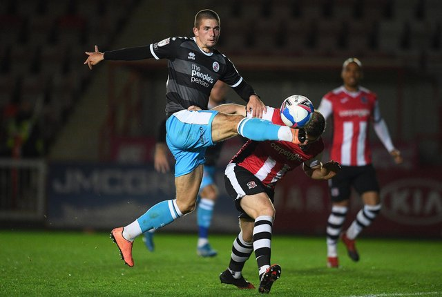 Max Watters of Crawley Town looks to break past Pierce Sweeney of Exeter City during the Sky Bet League Two match between Exeter City and Crawley Town at St James Park.