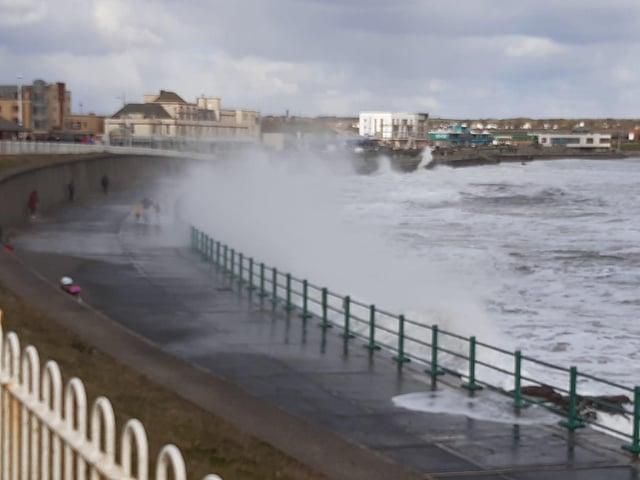 Waves crash over the promenade
