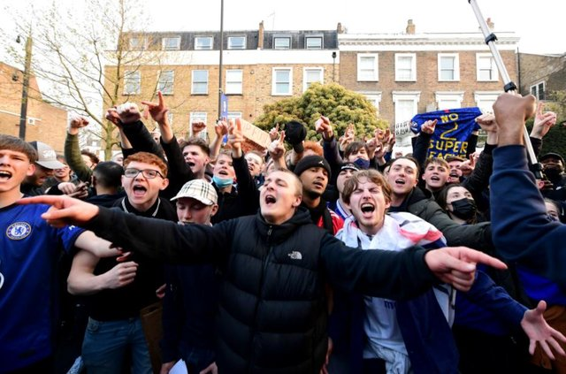 Fans react after first hearing Chelsea was preparing to withdraw from the Super League, outside Stamford Bridge, London.