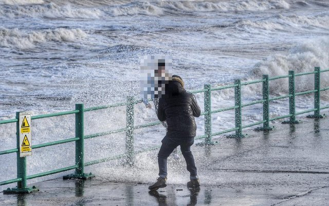 Pair take pictures as waves hit sea walls Picture by North News