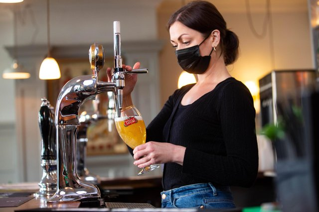Karine Makarova pulls a pint of Stella Artois behind the bar at the Red Lion & Sun in Highgate, London as outdoor hospitality reopens