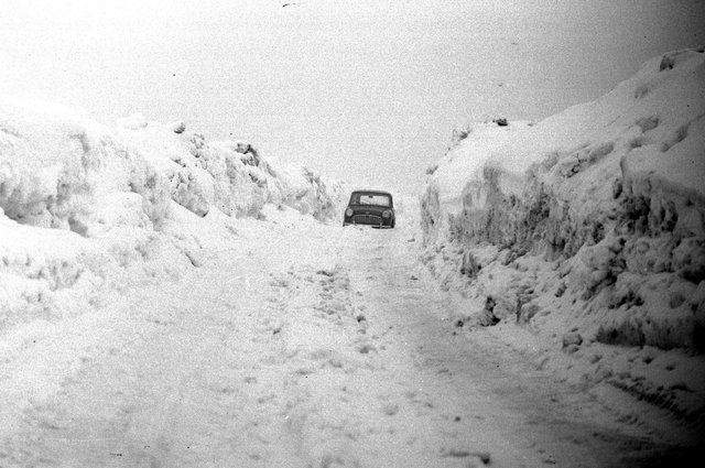A giant drift on the Durham to Sunderland road at West Rainton. This car is dwarfed by the wall of snow in 1963.
