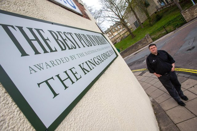 """The Kingslodge Inn general manager Darren Winder with the """"unauthorised"""" sign which Durham County Council have ordered the pub to remove."""