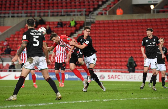 Charlie Wyke of Sunderland scores their side's first goal as he battles with Lewis Montsma of Lincoln City during the Papa John's Trophy semi-final match between Sunderland and Lincoln City.