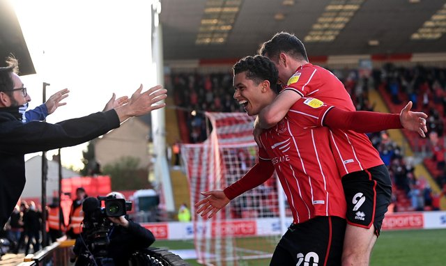 Brennan Johnson of Lincoln City celebrates after scoring their sides second goal with teammate Tom Hopper during the Sky Bet League One play-off semi-final first-leg match between Lincoln City and Sunderland.