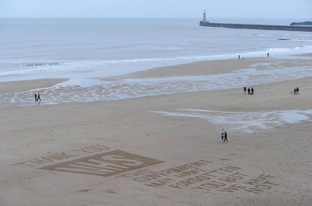A tribute to the NHS is drawn in the sand at Roker beach in Sunderland.