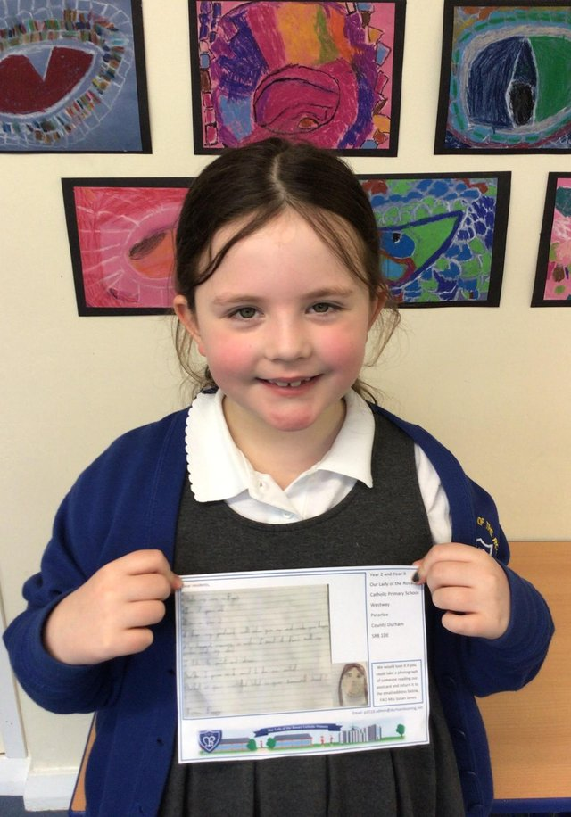 Poppy in Year 2, holding a post card of kindness, which was sent to a care home resident.